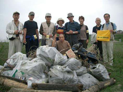 多摩川河川敷の清掃、収集したゴミの山の前で